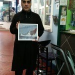 Eggelicious Ash Mistry holding a Tim Carroll painting of the Tented Market