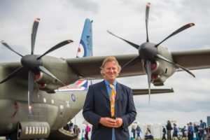 Famed aviation artist David Bent stands in front of a C-130 Hercules at the 2016 Royal International Air Tattoo.