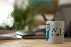 Wise-Bookkeeping_Desk and mug benefits of a bookkeeper to a small business