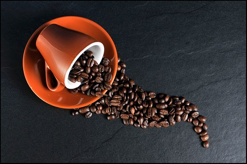 The history of coffee - coffee beans with cup and saucer
